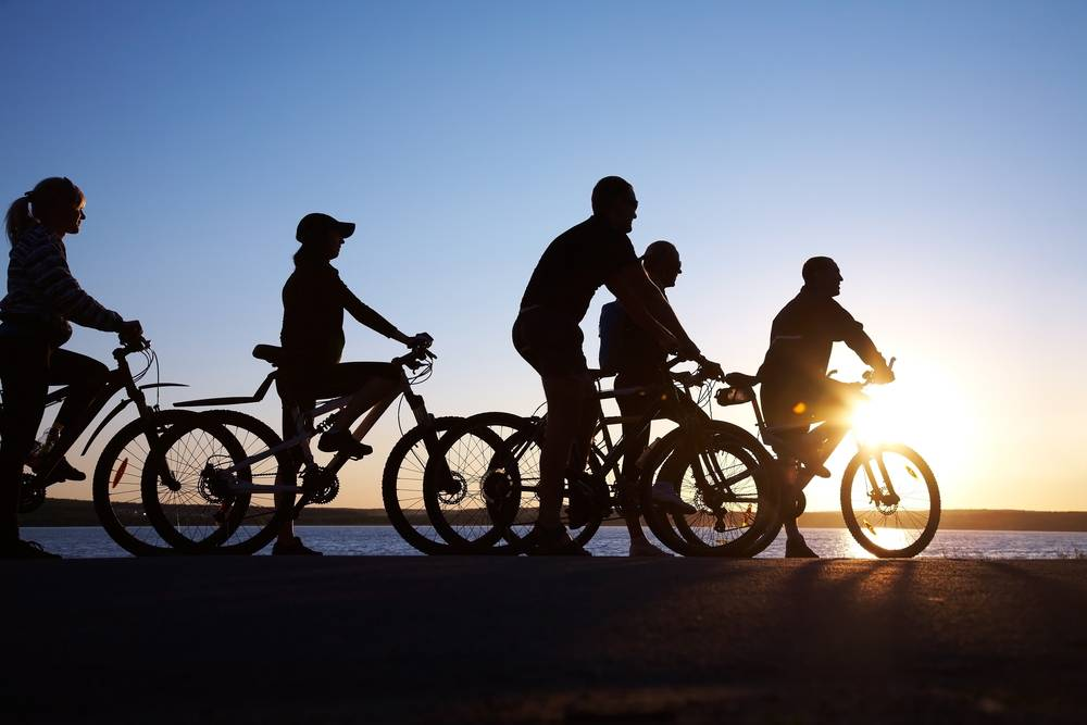 Image of sporty friends on bikes outside